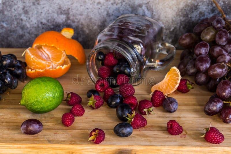 Frutas de la forma del tarro del Smoothie Uvas, frambuesa, cal, fondo oscuro fotos de archivo
