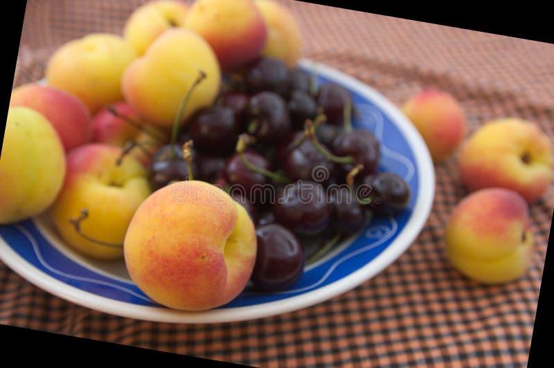 Frutas de la primavera en una placa en la tabla fotos de archivo libres de regalías