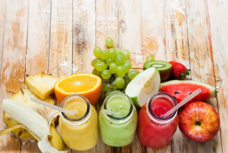 Frutas de las botellas del Smoothie tres de los jugos de la fila tropicales imágenes de archivo libres de regalías
