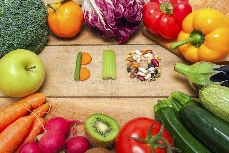 Frutas e legumes coloridas no fundo com a palavra bio foto de stock