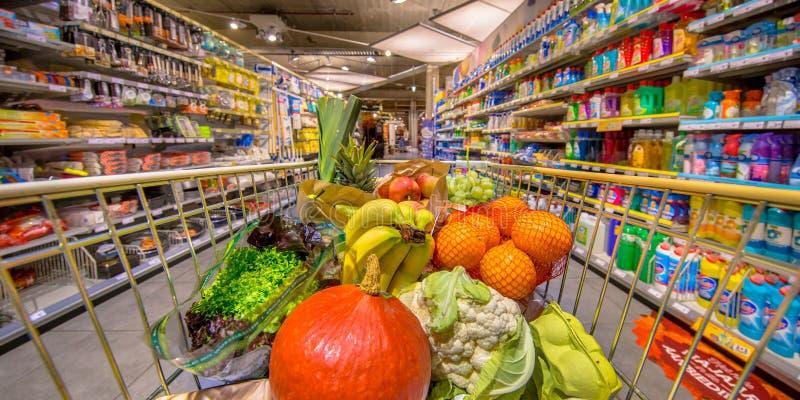 Frutas e legumes saudáveis no carro da loja de mantimento fotos de stock