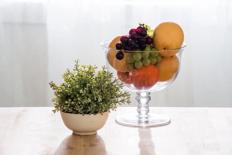 Frutas en bol de vidrio en la tabla de madera imágenes de archivo libres de regalías