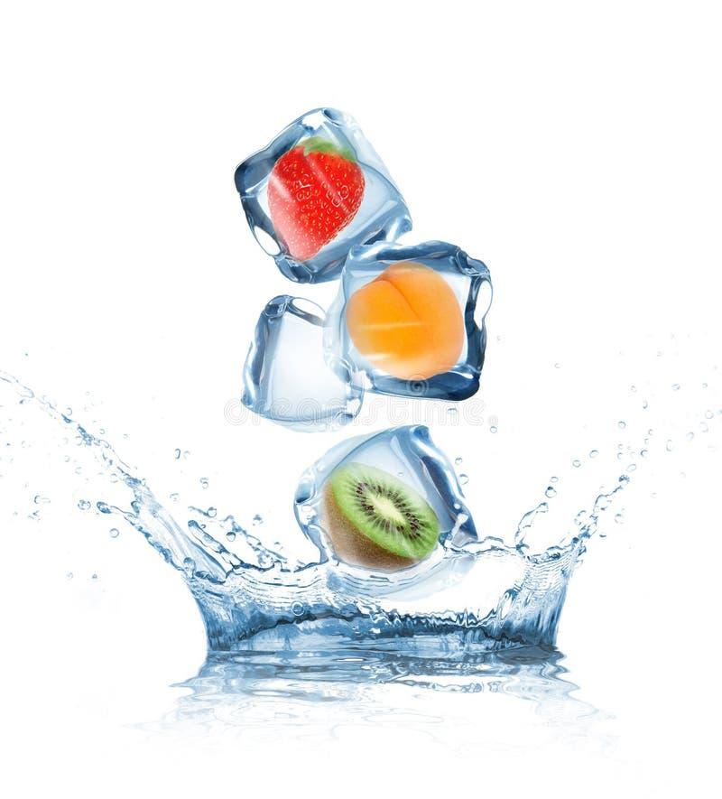 Frutas en los cubos de hielo que salpican en el agua foto de archivo libre de regalías