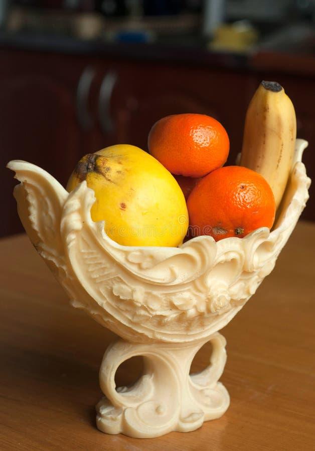 Frutas en un florero plástico elegante en la tabla de madera fotografía de archivo