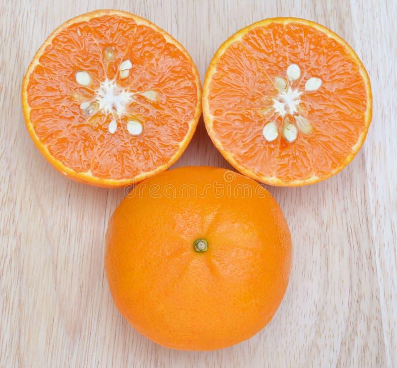 Frutas frescas anaranjadas en el fondo de madera del tablero foto de archivo