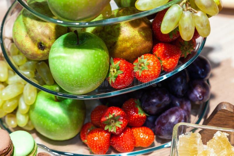 Frutas frescas brillantes del primer: manzanas, fresa, pera, uva, cubos en bol de vidrio, iris de las flores, macarrones, trufas  imagen de archivo libre de regalías