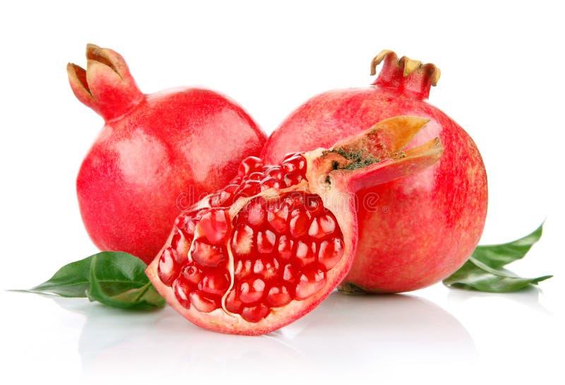 Frutas frescas da romã com as folhas do corte e do verde foto de stock royalty free