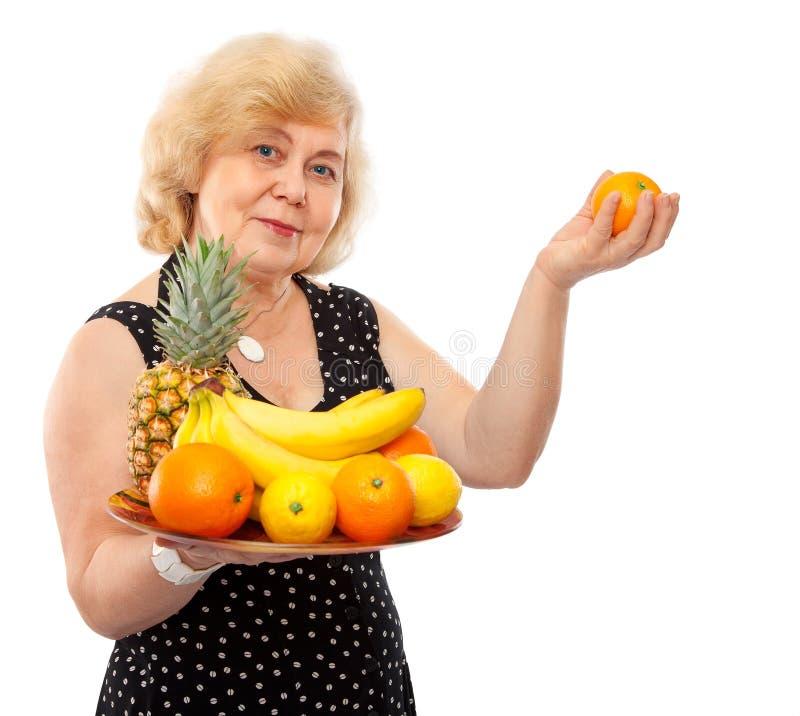 Frutas frescas do deleite feliz idoso da mulher foto de stock royalty free
