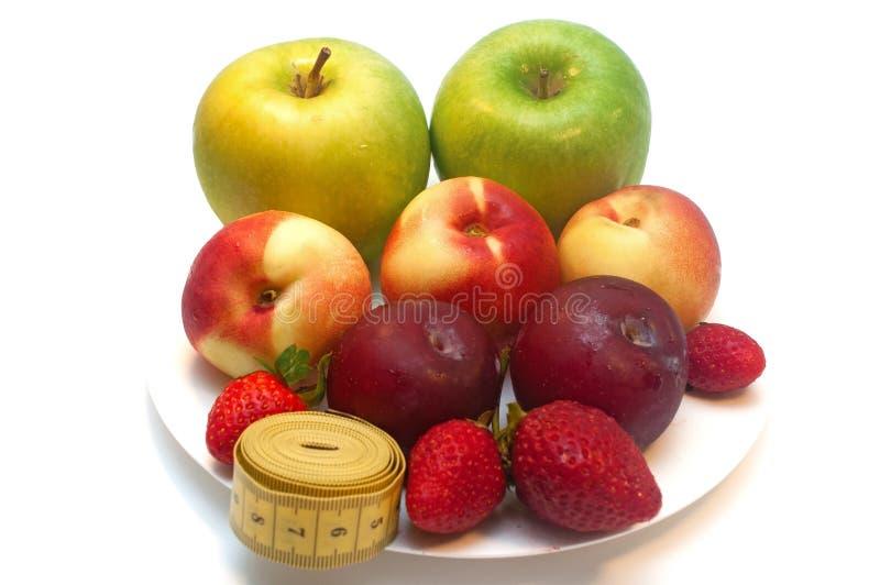 Frutas frescas en una placa aislada en el fondo blanco imagenes de archivo