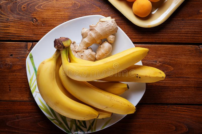 Frutas frescas plátano y albaricoques que ponen en la tabla de madera Endecha plana fotos de archivo