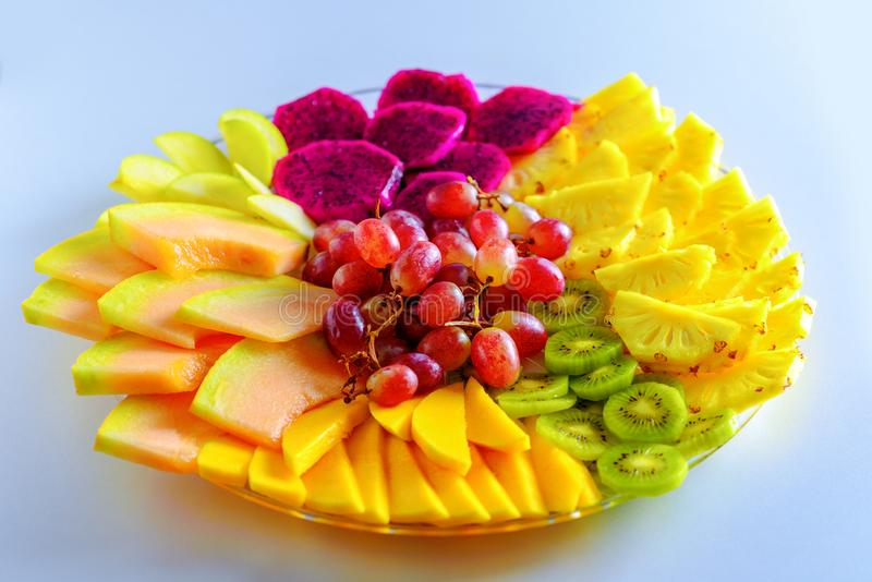 Frutas Fruto vermelho do dragão do pitaya, abacaxi, uvas, manga, melão, frutos tropicais diferentes na placa na tabela branca imagem de stock