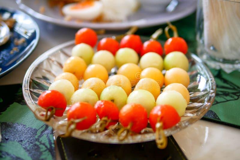 Frutas mezcladas del melón con muchos de color frutas frescas en la placa de cristal en la tabla tradicional del marple imagenes de archivo