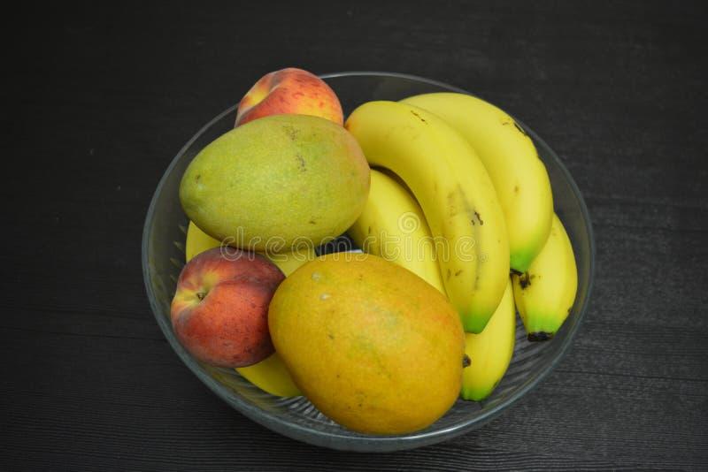 Frutas mezcladas en fondo de la tabla del cuenco imágenes de archivo libres de regalías