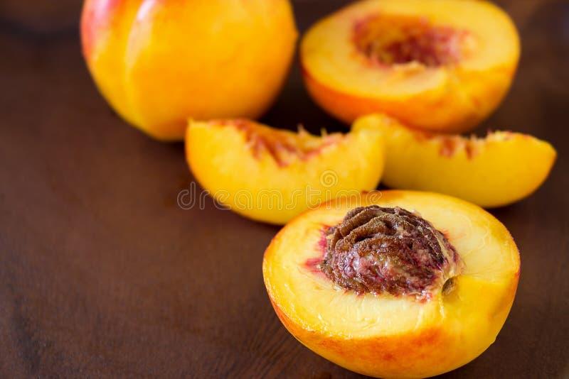 Frutas orgánicas de las nectarinas jugosas maduras enteras y rebanada en b de madera imagen de archivo