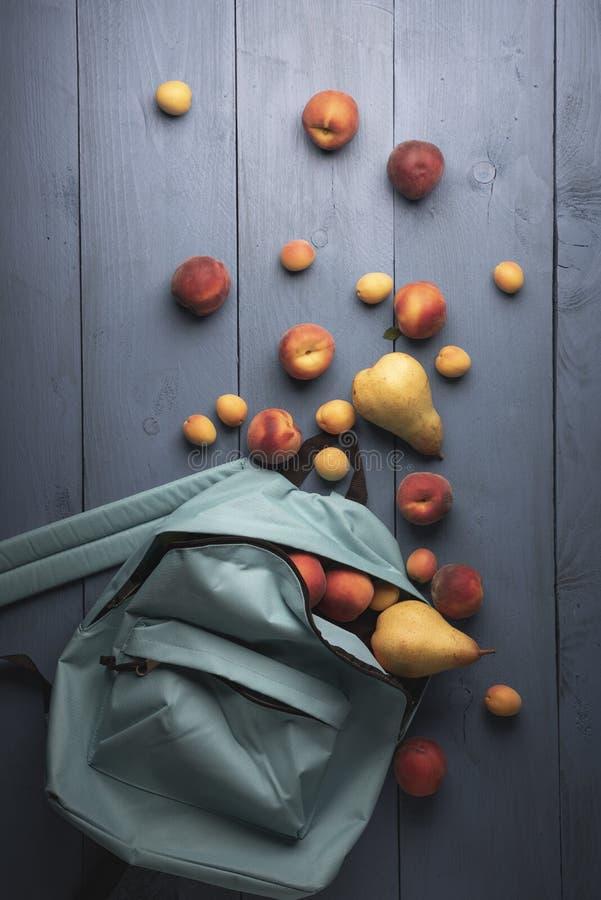 Frutas orgánicas en una mochila de la escuela Melocotones, albaricoques, y peras maduros foto de archivo libre de regalías