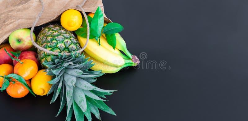 Frutas orgánicas sanas frescas compradas en mercado semanal en bolsa de papel marrón contra fondo oscuro de la tabla fotos de archivo libres de regalías