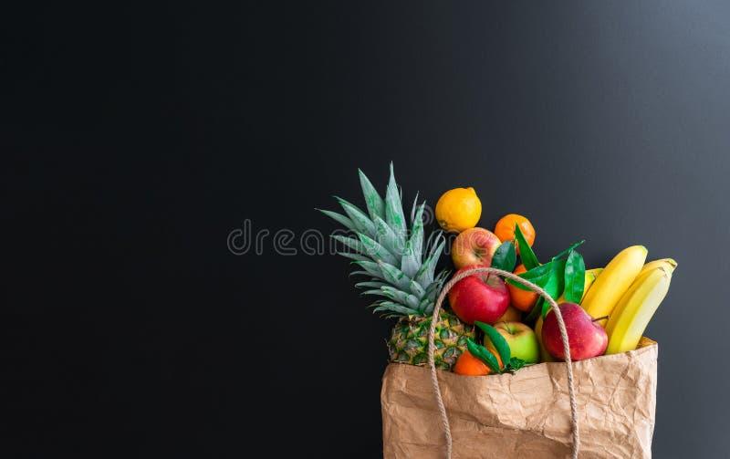 Frutas orgánicas sanas frescas compradas en mercado semanal en bolsa de papel marrón contra fondo oscuro de la tabla imágenes de archivo libres de regalías
