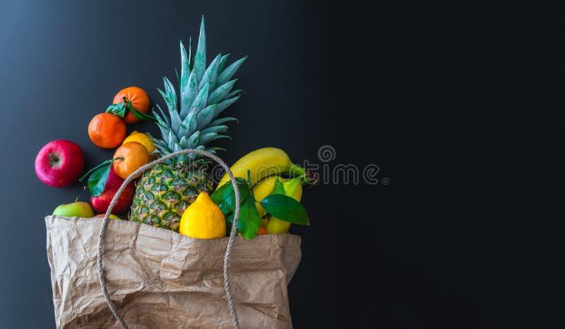 Frutas orgánicas sanas frescas compradas en mercado semanal en bolsa de papel marrón contra fondo oscuro de la tabla imagenes de archivo