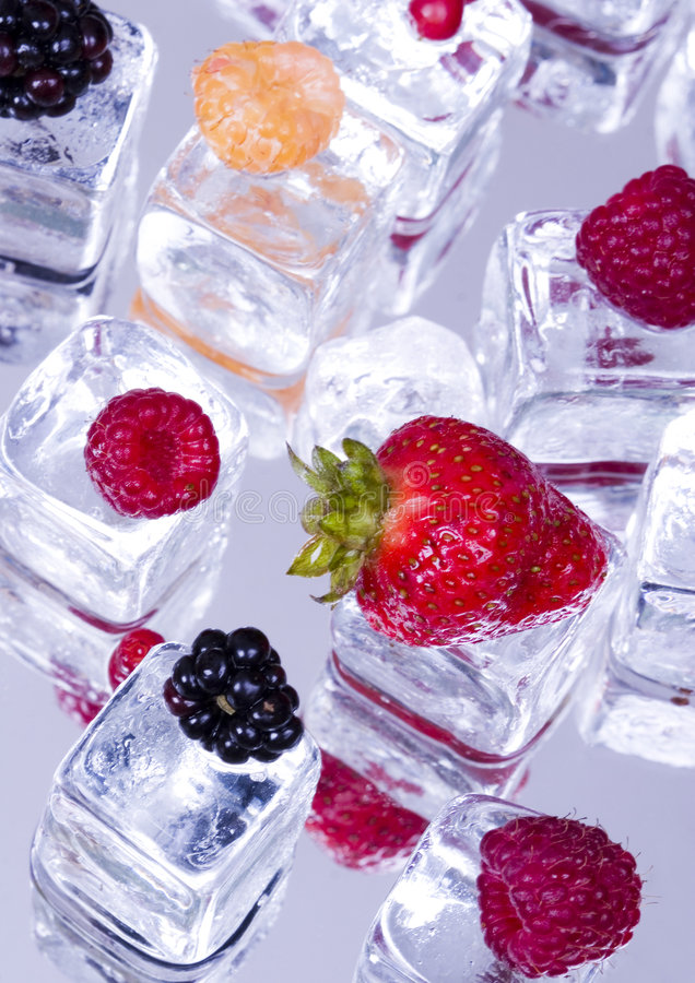 Frutas pequenas entre cubos de gelo imagem de stock royalty free