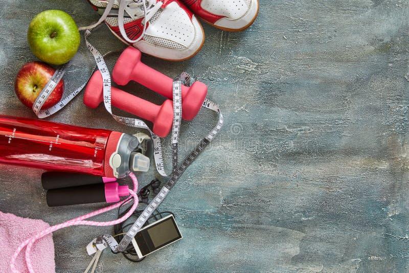 Frutas, pesas de gimnasia, una botella de agua, cuerda, zapatillas de deporte y un metro en un azul con el fondo del divorcio imagen de archivo