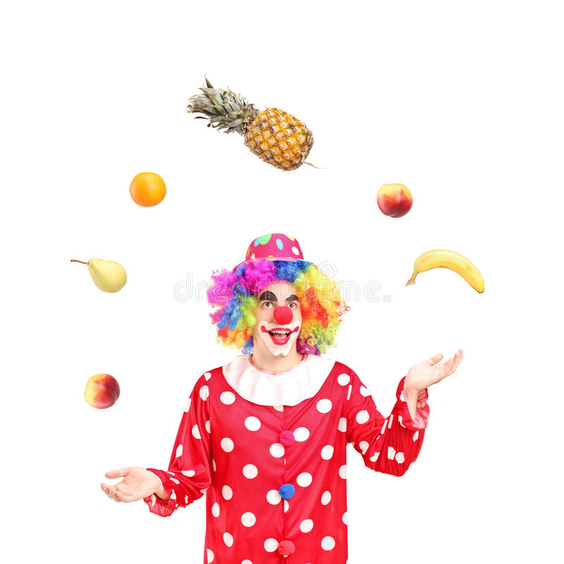 Frutas que hacen juegos malabares sonrientes de un payaso fotografía de archivo libre de regalías