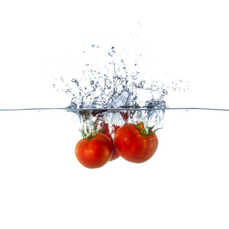 Frutas rojas frescas del tomate que se hunden en agua foto de archivo