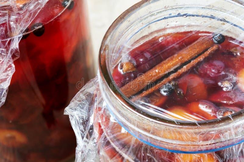 Frutas rojas preservadas con las especias en los tarros de cristal imagen de archivo libre de regalías