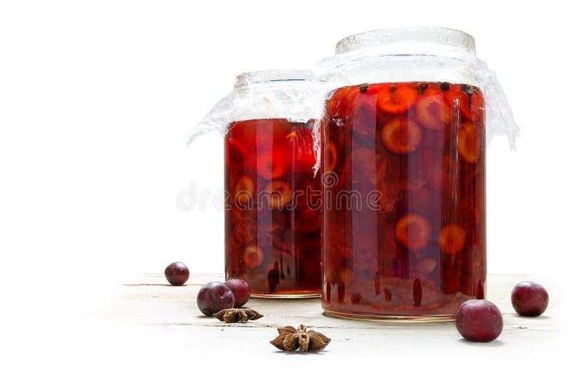 Frutas rojas preservadas en dos tarros de cristal, contra blanco foto de archivo libre de regalías