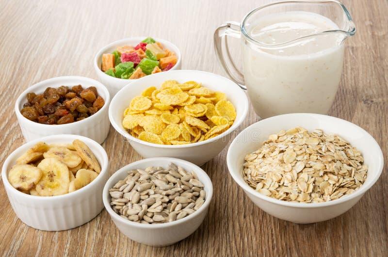 Frutas secadas, avenas, harina de avena, semillas de girasol, microprocesadores del plátano en los cuencos, jarra con el yogur e imagen de archivo libre de regalías