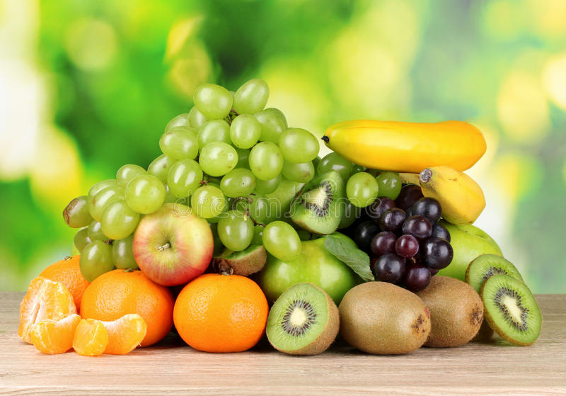 Frutas suculentas maduras na tabela de madeira no verde imagem de stock