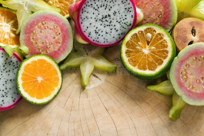 Frutas tropicales mandarina, guayaba, fruta del dragón, fruta de estrella, zapote en el fondo de madera imágenes de archivo libres de regalías