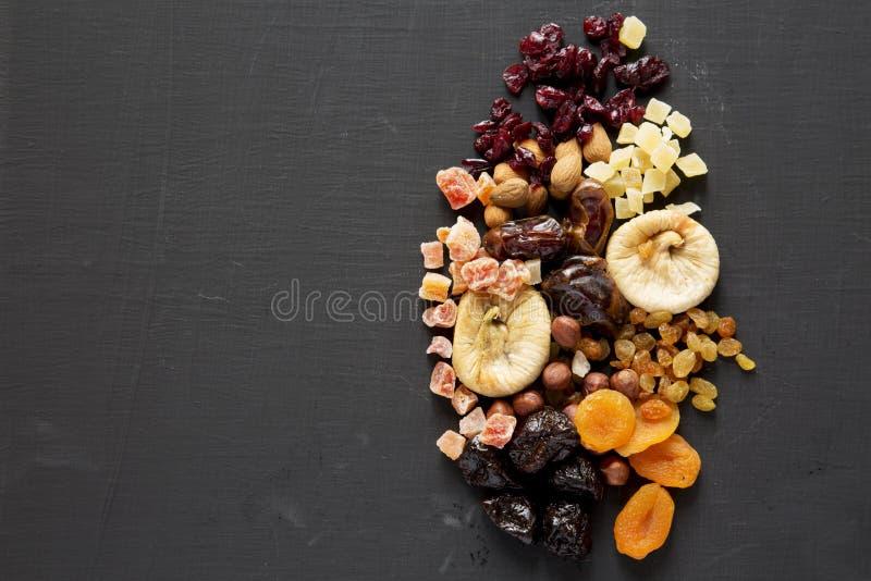 Frutas y mezcla secadas de la nuez en el fondo negro, visi?n superior overhead Copie el espacio fotos de archivo libres de regalías