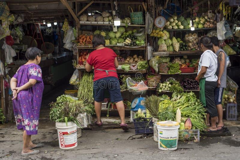 Frutas y verduras de la compra de los clientes en una tienda de ultramarinos de la calle en Manila imagen de archivo