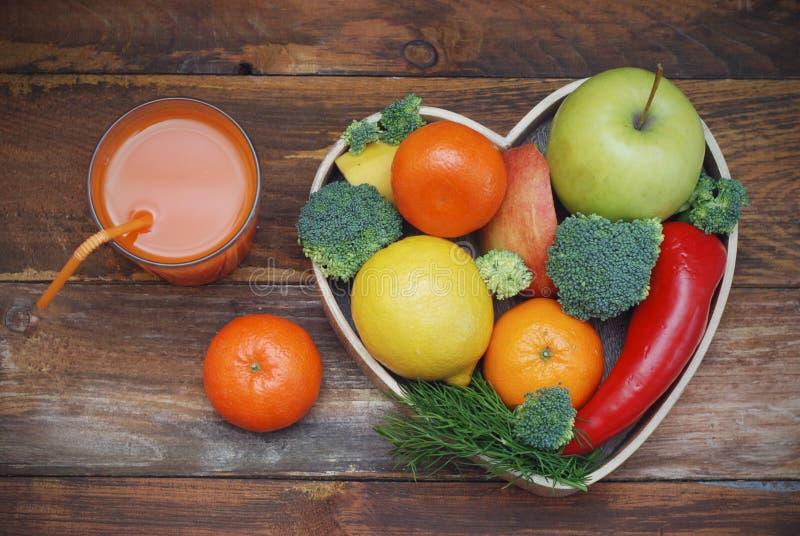 Frutas y verduras en caja de madera en forma de corazón Bróculi, manzanas, pimienta, mandarina y vidrio de jugo sobre fondo de ma fotos de archivo