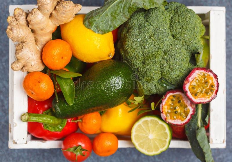 Frutas y verduras frescas en una caja de madera blanca Un veg sano foto de archivo
