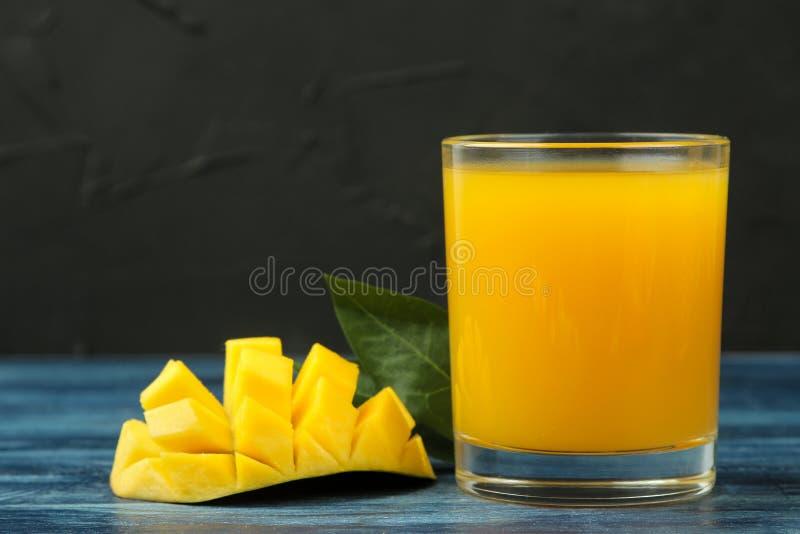Fruto da manga e fatias e suco frescos maduros da manga em um vidro em uma tabela de madeira azul Fruta tropical imagens de stock