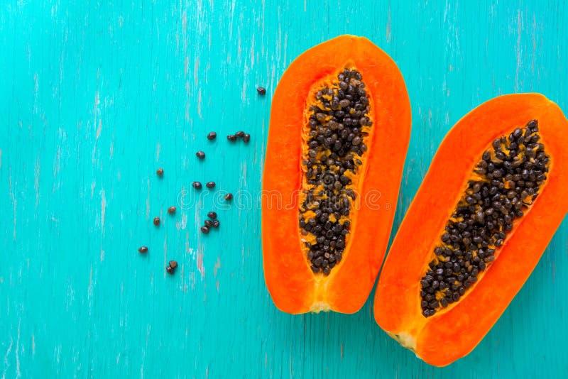 Fruto da papaia no fundo de madeira Fatias de papaia doce no fundo de madeira, papaia partidas ao meio com folhas, foto de stock