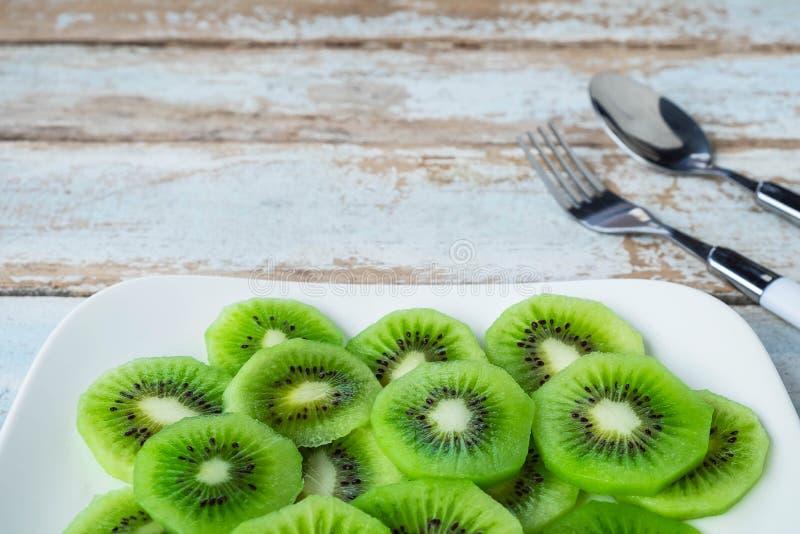 Fruto de quivi fresco em uma placa em uma tabela de madeira fotos de stock