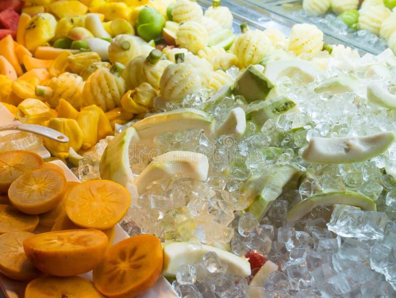 Fruto e abacaxi do caqui misturados com o cubo de gelo fotos de stock royalty free