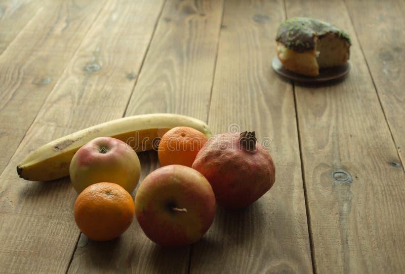 Fruto e filhós com chocolate em um fundo de madeira imagem de stock royalty free