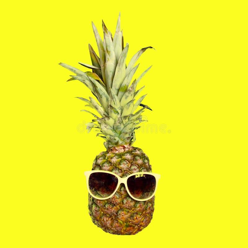 Fruto engraçado do abacaxi nos óculos de sol no fundo amarelo brilhante Férias de verão e tema do partido imagens de stock royalty free