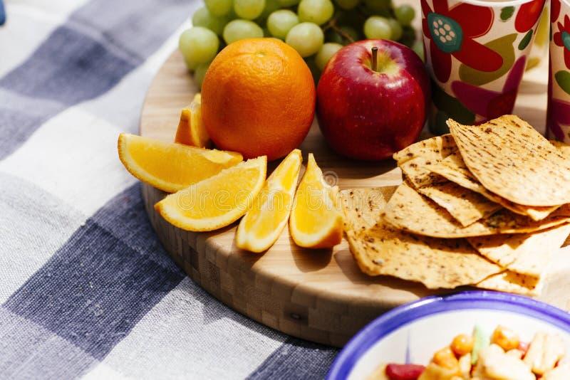 Fruto fresco e petiscos na cobertura do piquenique imagem de stock royalty free