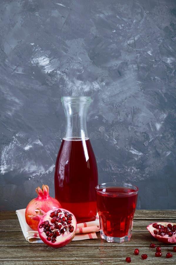 Fruto, garrafa e vidro maduros da romã do suco fresco da romã na tabela de madeira foto de stock
