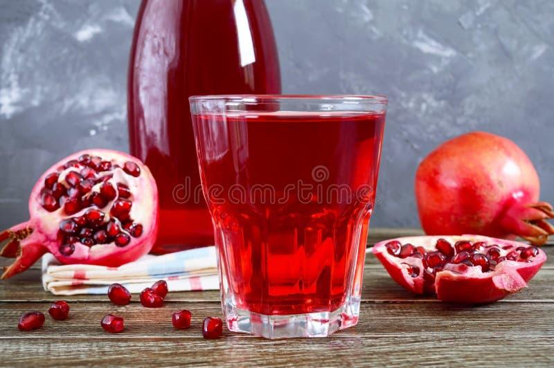 Fruto, garrafa e vidro maduros da romã do suco fresco da romã na tabela de madeira imagens de stock royalty free