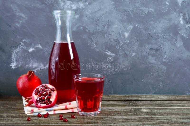 Fruto, garrafa e vidro maduros da romã do suco fresco da romã na tabela de madeira Conceito saudável comer imagem de stock