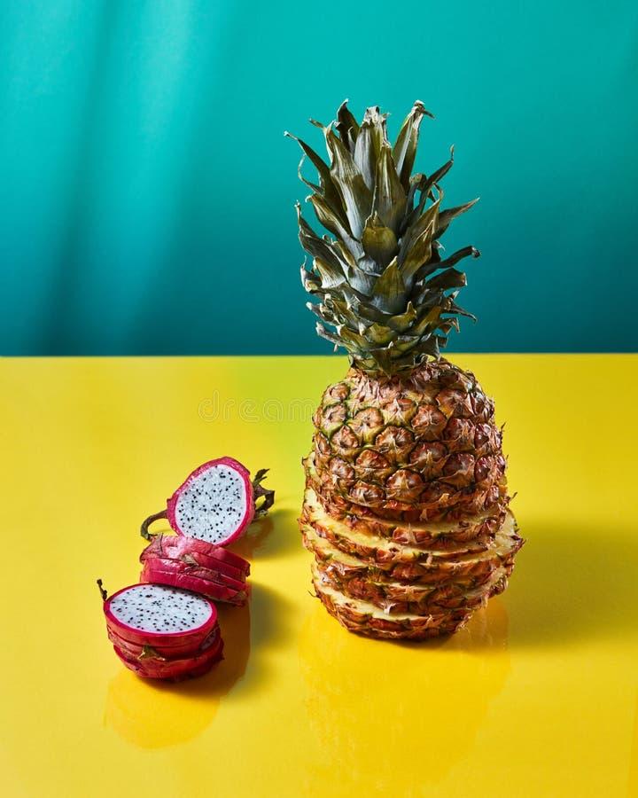 Fruto inteiro do fruto tropical do abacaxi o único e do dragão, pitaya compôs do sliceson em um fundo verde-amarelo do duotone imagens de stock royalty free