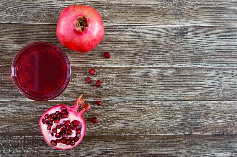 Fruto maduro da romã e um vidro do suco da romã na tabela de madeira Conceito saudável comer imagem de stock