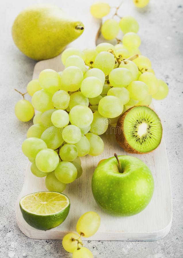 Fruto tonificado verde orgânico cru fresco na placa de desbastamento branca no fundo de pedra da cozinha Pera e uvas com quivi e  fotografia de stock royalty free