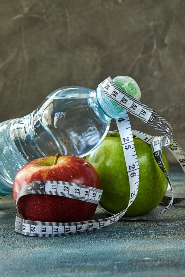 Fruto, uma garrafa da água, um medidor em um azul com um fundo do divórcio fotografia de stock