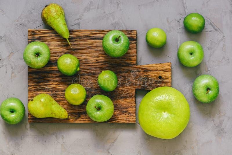 Fruto verde, maçãs, cal, pera, oroblanco em uma placa de corte Coleção das frutas imagens de stock